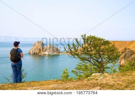 A woman backpacker looks at the Shamanka Rock, Cape Burhan on Olkhon Island. Lake Baikal, Siberia, Russia
