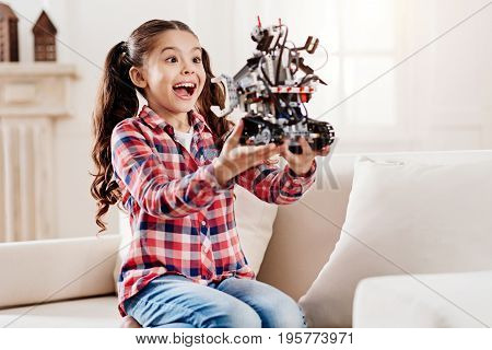 I am surprised. Happy girl keeping her mouth wide opened and sitting in semi position on the sofa while holding her robot