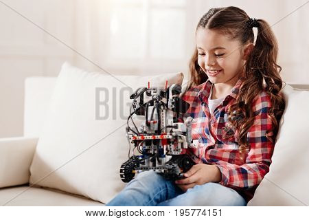 Good mood. Cheerful child expressing positivity and looking downwards while sitting on white sofa