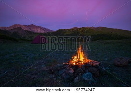 Tent And Burning Camp Fire At Dusk On The Mountains. Summer Adventures And Exploration In The Alps.