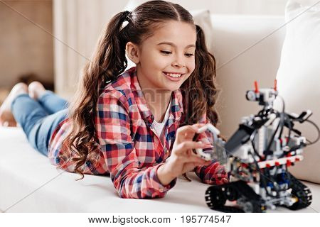 Moment of happiness. Positive delighted little female person keeping smile on her face and bowing head while playing with robot