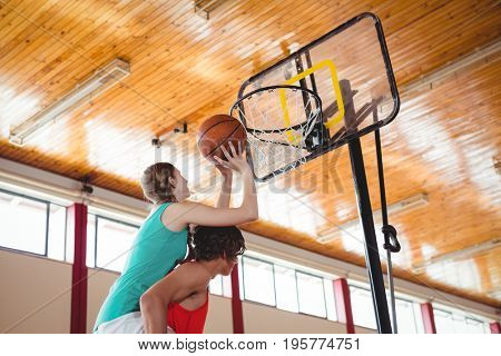 Man assisting female friend while playing basketball in court