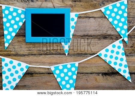 Blue And White Spotted Bunting Flags Hanging Against Rustic Timber Background With Blank Framed Blac