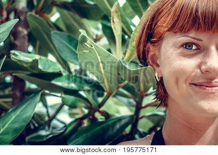Close up of half face portrait of young beautiful woman on green leafs back. Tropical island Bali. Beautiful fashion spa scene.