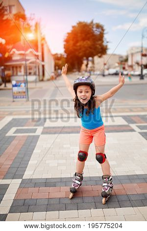 Cute little girl learning to roller skate in city skate park on beautiful summer day. Happy kid ride and play in the park.