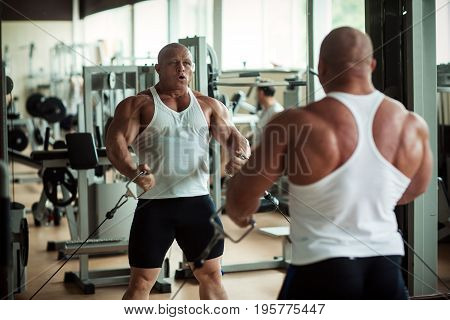 A man is engaged in a gym in front of a mirror