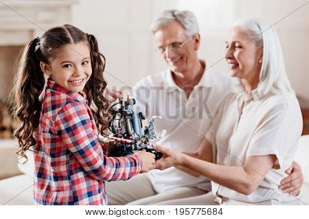 Weekend with grandparents. Positive delighted child standing in semi position on the foreground and holding robot in both hands while looking forward