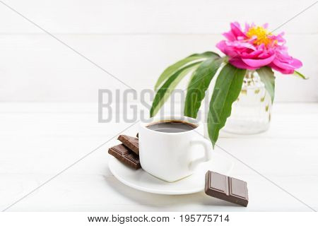 White Cup Of Coffee With Flower In Vase And Chocolate On Whte Wooden Background