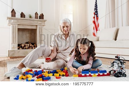 Be attentive. Serious girl sitting with crossed legs and bowing head while playing with meccano