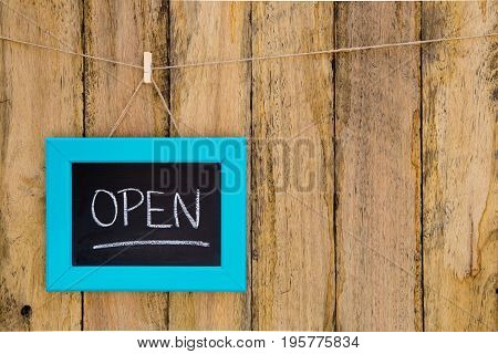 Open - Handwritten In Chalk On Framed Blackboard Sign Hanging Against Rustic Timber Background