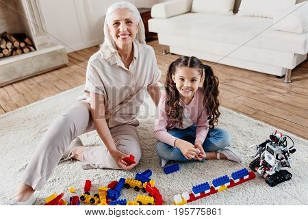 Have a look. Delighted woman looking straight at camera while expressing positivity and playing with grandchild