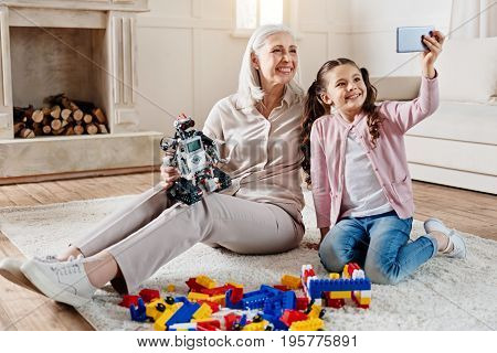 Selfie time. Smiling woman holding robot in right hand and siting near her granddaughter while looking upwards at camera
