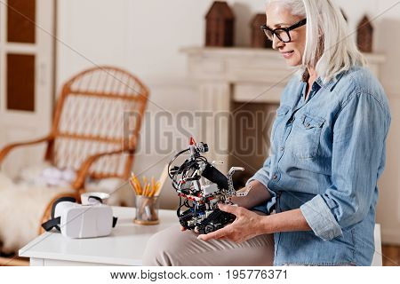 Happy old age. Delighted grandma siting on the table in semi position and bowing head while looking at robot of her granddaughter