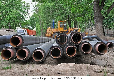 The process of laying of engineering heating systems. Many black plastic pipes lying on the ground and excavator in the background.