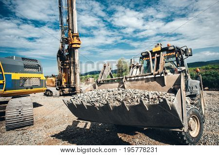 Industrial Heavy Duty Bulldozer Moving Gravel On Highway Construction Site. Multiple Industrial Mach