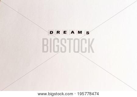 Word dreams written in black letters on neutral background