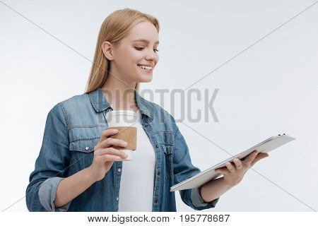 Coffee break. Pleased girl keeping smile on her face and looking downwards at folder while standing isolated on white background