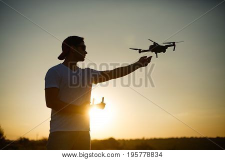 Silhouette of a man catching drone with one hand and remote controller in another hand on sunset. Safe quadcopter landing on the pilot's palm. Sun flares