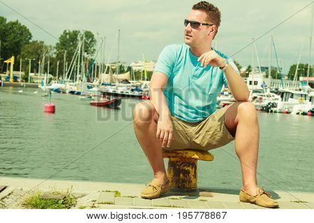 Summertime vacation adventure concept. Man spending his free time walking on marina sightseeing during summer guy sitting on bitt. poster