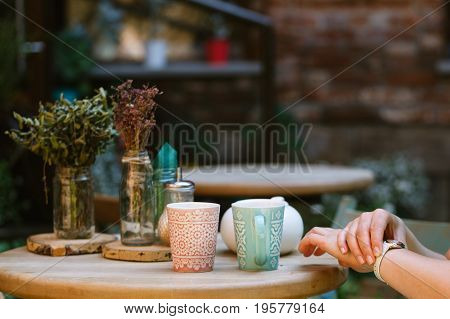 Someone Is Getting Late. Woman Checking Time On His Watch While Waiting For Him Having A Cup Of Coff