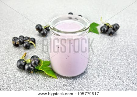Milk cocktail with black currant in a glass jar with berries on the background of a gray stone table