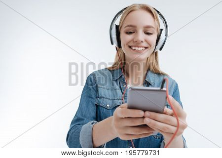 Keep smiling. Positive delighted young woman expressing positivity while looking downwards at her mobile phone and wearing headphones