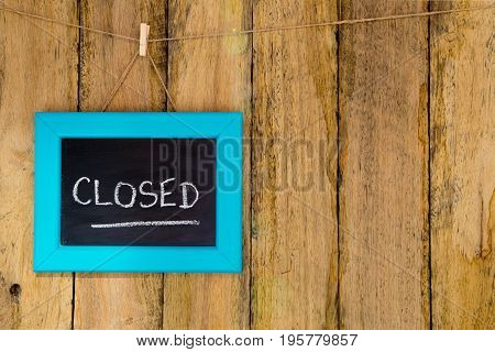 Closed - Handwritten In Chalk On Framed Blackboard Sign Hanging Against Rustic Timber Background