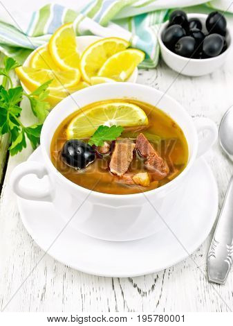 Soup saltwort with lemon, meat, pickles, tomato sauce and olives in a white bowl, towel, parsley on a wooden board background