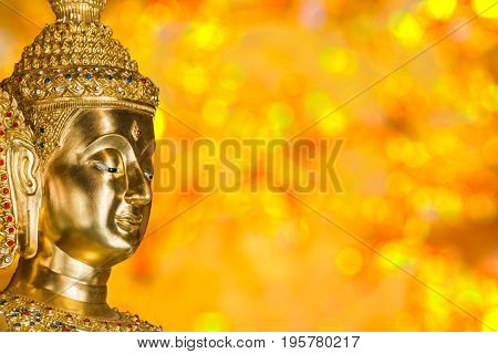 Head of golden Buddha Image with bokeh blurred background in Buddhist church
