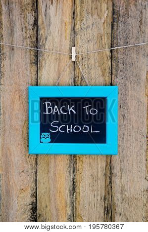 Back To School Hand Written In Chalk On Blackboard With Blue Frame Hanging Against Rustic Timber Woo