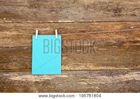 Blue Colored Paper - Cardboard On Clothespins Hanging Againts Old Timber Plank Background