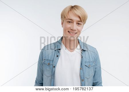 Watch me. Attractive male person standing isolated on white and keeping smile on his face while being happy now