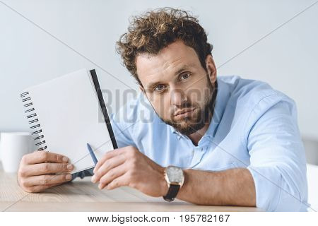 Portrait Of Businessman Sitting At Workplace And Pointing At Blank Notebook In Hand