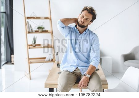 Businessman Having Neck Ache While Sitting On Table In Modern Office