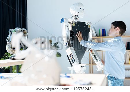 Nice job. Dark-haired little boy standing near a human robot and touching its front part while a blurred image of a white warrior robot toy standing on the table in the foreground