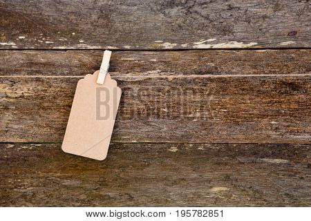 Paper - Cardboard Label Hanging On Clothespin Against Old Wooden Background