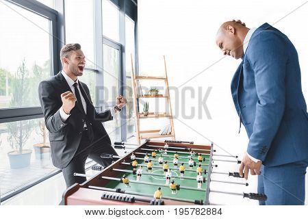 Excited Businessman Playing Table Football With Coworker In Office