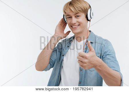 I recommend it. Attractive man raising his thumb up and looking at camera while touching headphones