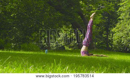 Young woman doing yoga exercises in the park. Sarvangasana
