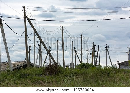 many telephone and electricity poles in a rural location and wire