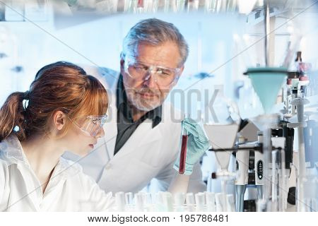 Health care researchers working in life science laboratory. Young female research scientist and senior male supervisor observing red indicator color shift in tube due to change of pH in solution .