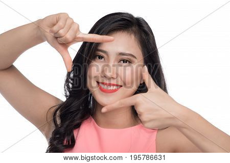Beautiful woman making a frame with fingers in front of face