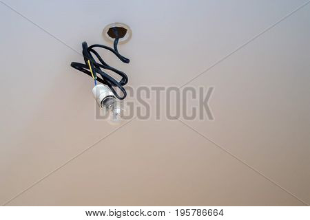 Closeup image of light bulb with black cord hanging from ceiling