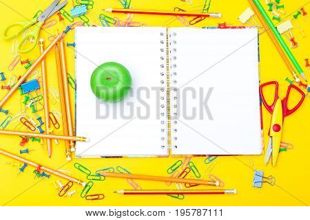 Notebook with school supplies on a yellow background. mock up