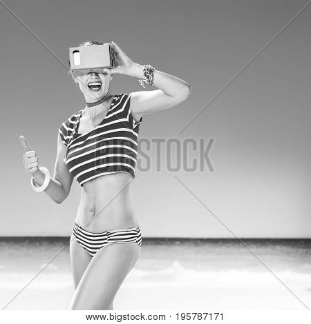 Perfect summer. Portrait of smiling active woman on the seacoast showing thumbs up and wearing cardboard virtual reality gear