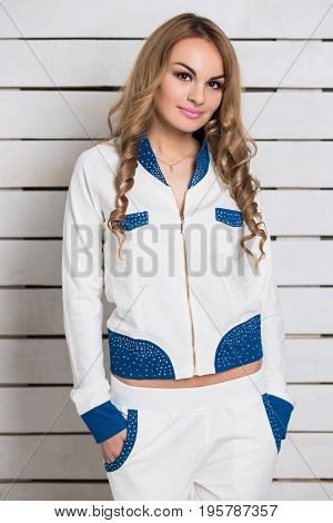 Portrait of nice blonde in white and blue clothes posing near the wall