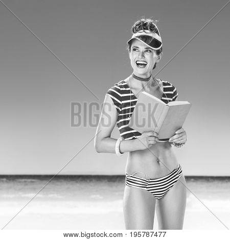 Happy Active Woman On Seacoast With Book Looking At Copy Space