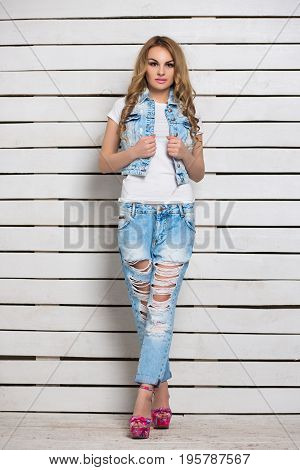 Sexy blond woman posing in blue jeans near white wooden wall