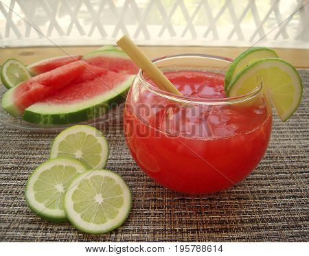 Watermelon smoothie in the round bowl on a veranda table.