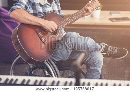 Lyric mood. Disabled musician holding guitar in both hands keeping his right leg on the left one while singing song